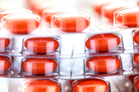 packs of pills: Red tablets in plastic packing as background Stock Photo