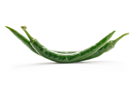 chilly: Two green hot chilly peppers on white background Stock Photo