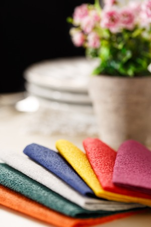 colorful still life: Still life with colorful paper table napkins, flowers and plates Stock Photo