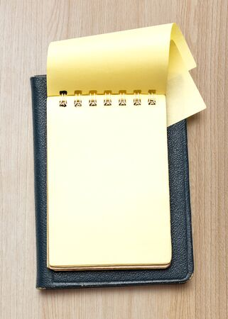 yellow notepad: Single yellow notepad on the wooden background