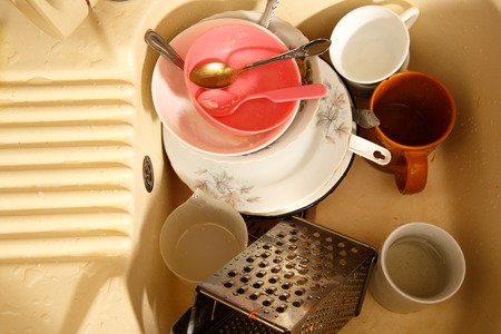 dirty dishes: Dirty dishes in kitchen sink in closeup