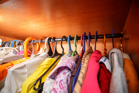 clotheshanger: Photo of clothes hangs in wooden cupboard