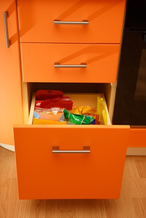 Orange wooden kitchen drawers with one open Stock Photo