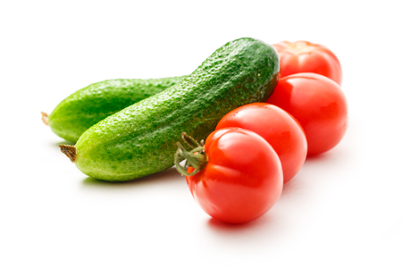Fresh cucumbers and tomatoes on white background