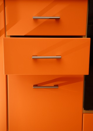 drawers: Orange wooden kitchen drawers as background closeup Stock Photo