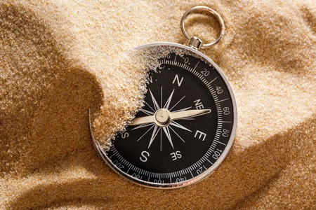 Black compass with beach sand in closeup