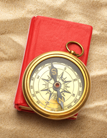 closed book: Red closed book with retro compass on sand Stock Photo
