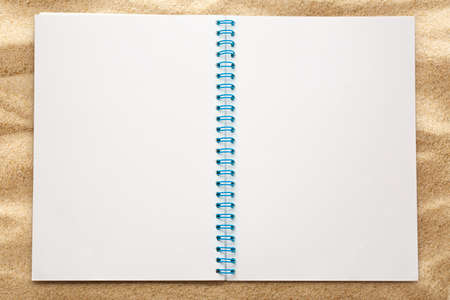 notebook page: Blank open notepad on the sand background