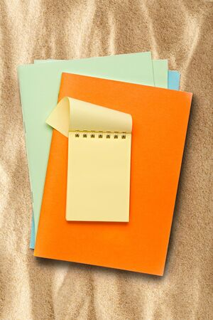 yellow notepad: Open yellow notepad on colored pieces of paper on sand Stock Photo