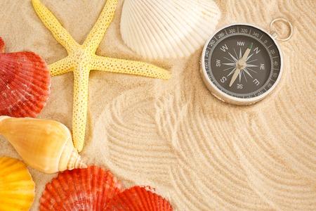 seastar: Compass, seastar and seashells in sand closeup