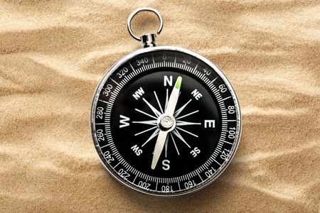 ravel: Black compass on the sand background closeup Stock Photo