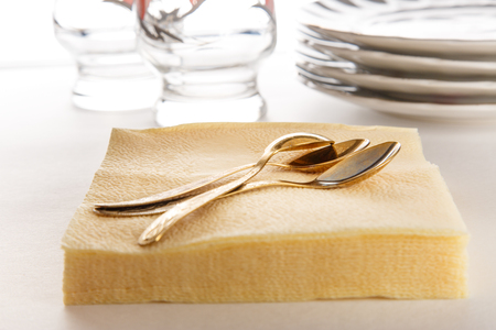 paper plates: Stack of paper napkins with spoons, plates and glasses