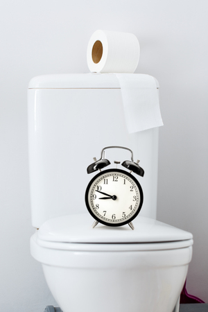 hygienic: Hygienic paper on white toilet tank and alarm clock Stock Photo