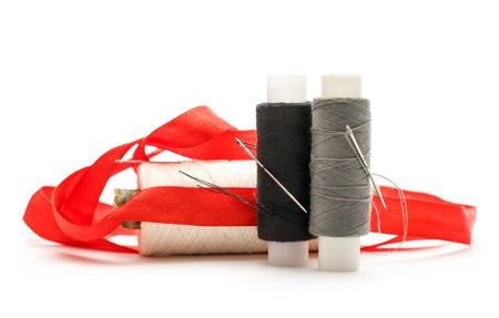 metal filament: Thread bobbins and needles on white background Stock Photo