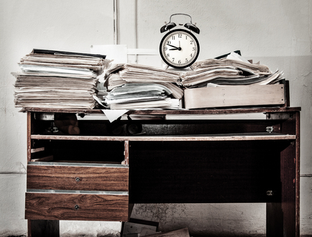 old desk: Messy workplace with stack of old paper and alarm clock