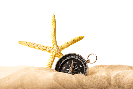 Fingerfish and compass in sand on white background