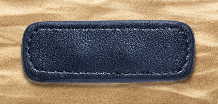 leather label: Blue blank leather label on sand background