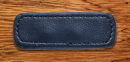 leather label: Blue blank leather label on wooden background