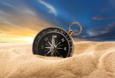 Compass in sand on the sunset background