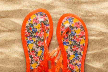 swimming shoes: Female beach sandals on sand background closeup Stock Photo