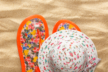 swimming shoes: Female sun hat and beach sandals on sand background