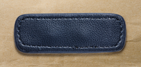 leather label: Blue blank leather label on paper background