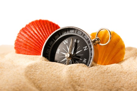 Sea shells and compass in sand on white background