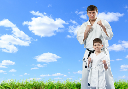 Karate master with his young student on blue sky background