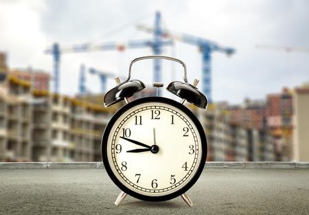 puntualidad: Clock on buildings and cranes background closeup Foto de archivo