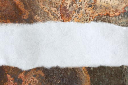 ripped metal: Ragged piece of paper on rusty background Stock Photo