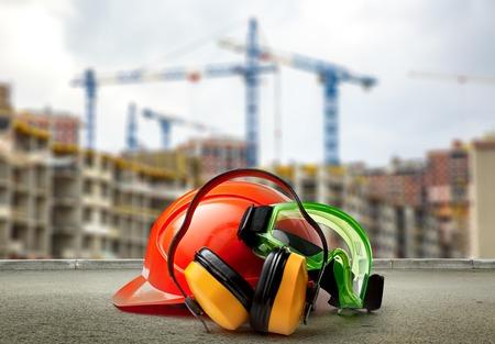 casco rojo: Red helmet and earphones on buildings background closeup