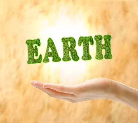 Female hand holding word earth made of green grass