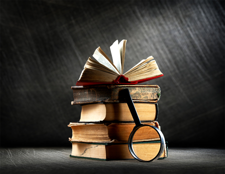 scratchy: Pile of old books with magnifying glass on steel scratchy background