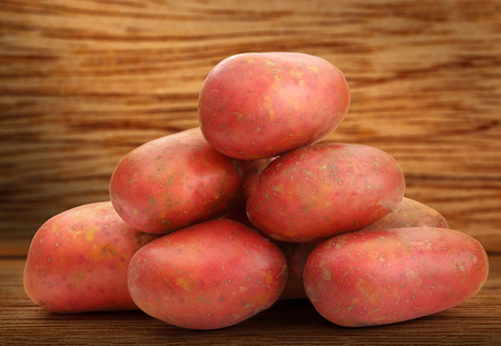 spud: Fresh whole potatoes on the wooden background