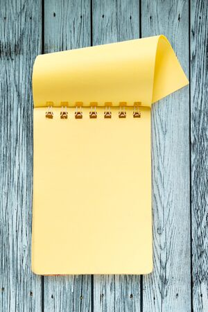 yellow notepad: Blank yellow notepad on the wooden background Stock Photo