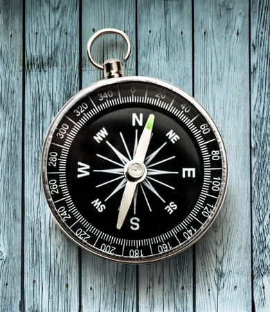 Black compass on wooden background in closeup