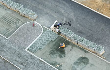 constructing: Workers constructing pavement with tile view from above