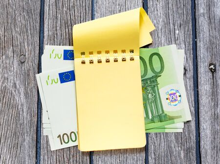yellow notepad: One hundred euro banknotes and blank yellow notepad Stock Photo