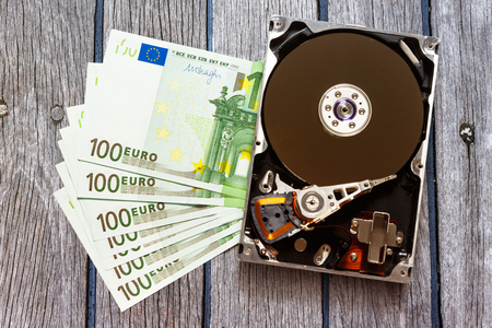 optical disk: One hundred euro banknotes and hardisk in closeup Stock Photo