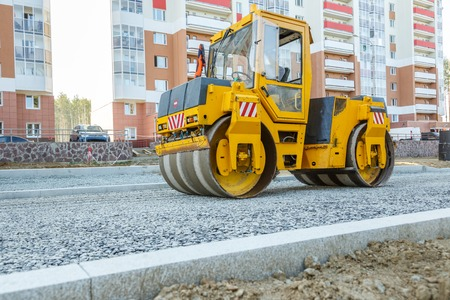 Road roller working at road construction site Imagens