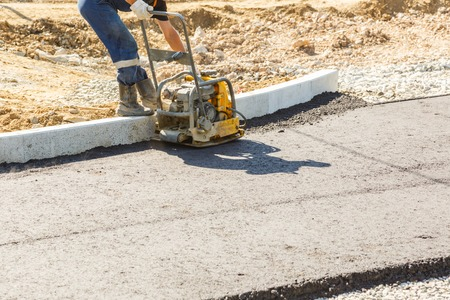 compacting: Worker use vibratory plate compactor compacting asphalt at road repair