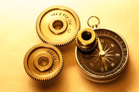 Three steel cogwheels with compass in closeup