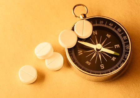 White aspirin pills and compass in closeup