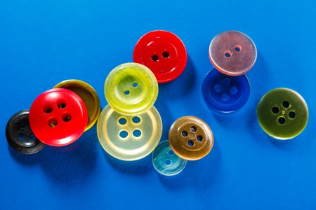 Colourful buttons on blue background in closeup Stock Photo