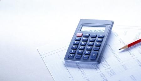 operating key: Operating budget, calculator and pencil in closeup