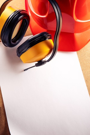 Red helmet, yellow earphones and blank sheet of paper