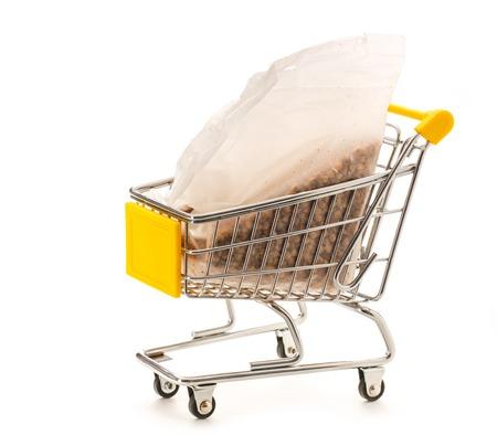 pushcart: Packet of dry buckwheat in small supermarket pushcart closeup