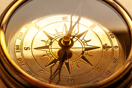 Vintage metal compass in toning light closeup