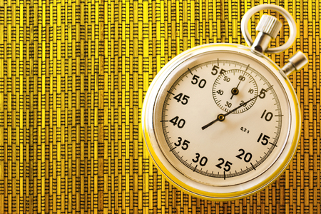 Stopwatch on yellow background in closeup Stock Photo