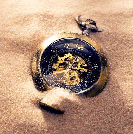 Pocket watch in beach sand light closeup